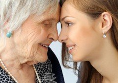 Old and young woman touching foreheads